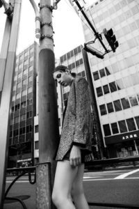 fashion model wearing golden jacket and black skirt walking under a traffic light in tokyo