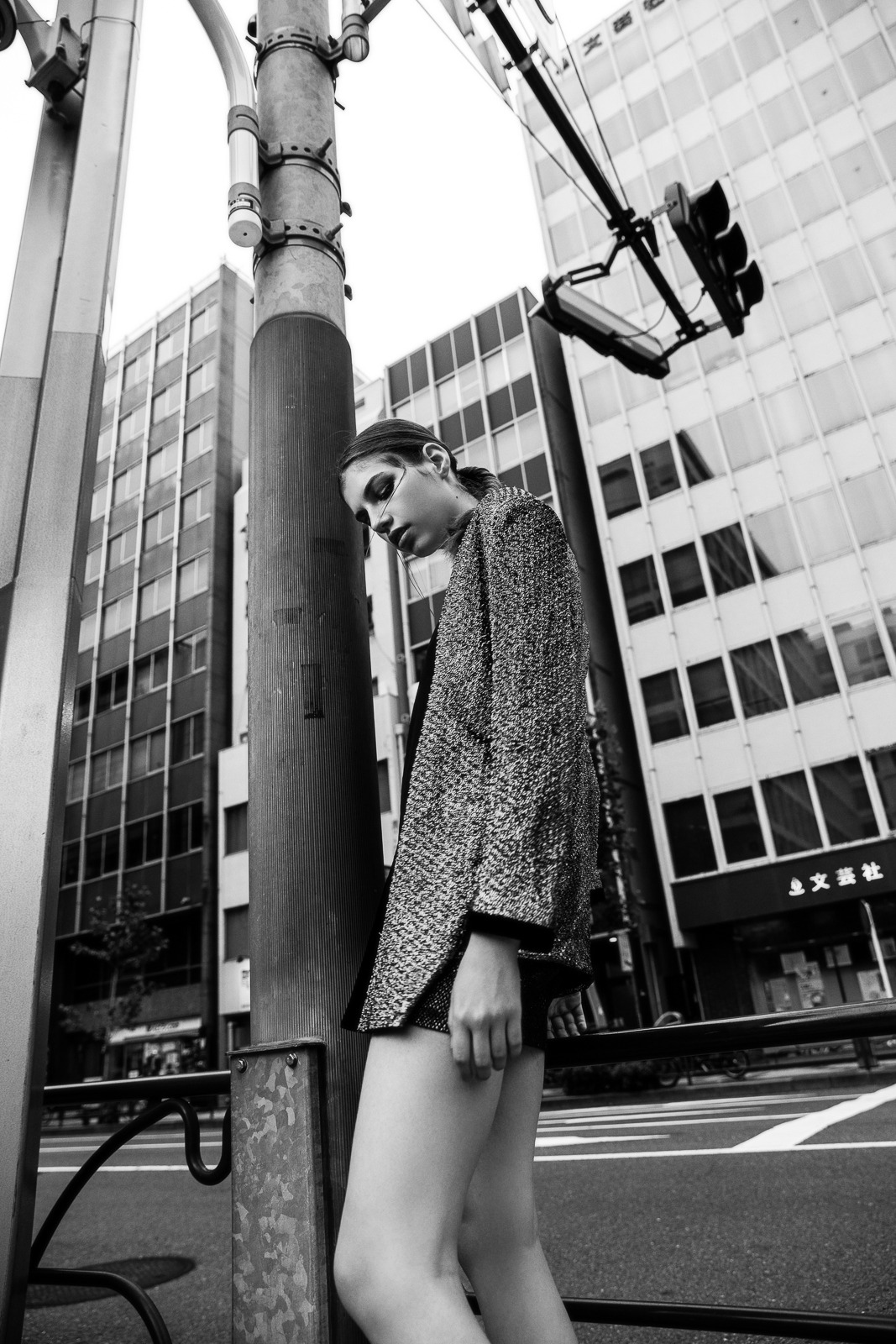 fashion model wearing golden jacket and black skirt walking under a traffic light in tokyo