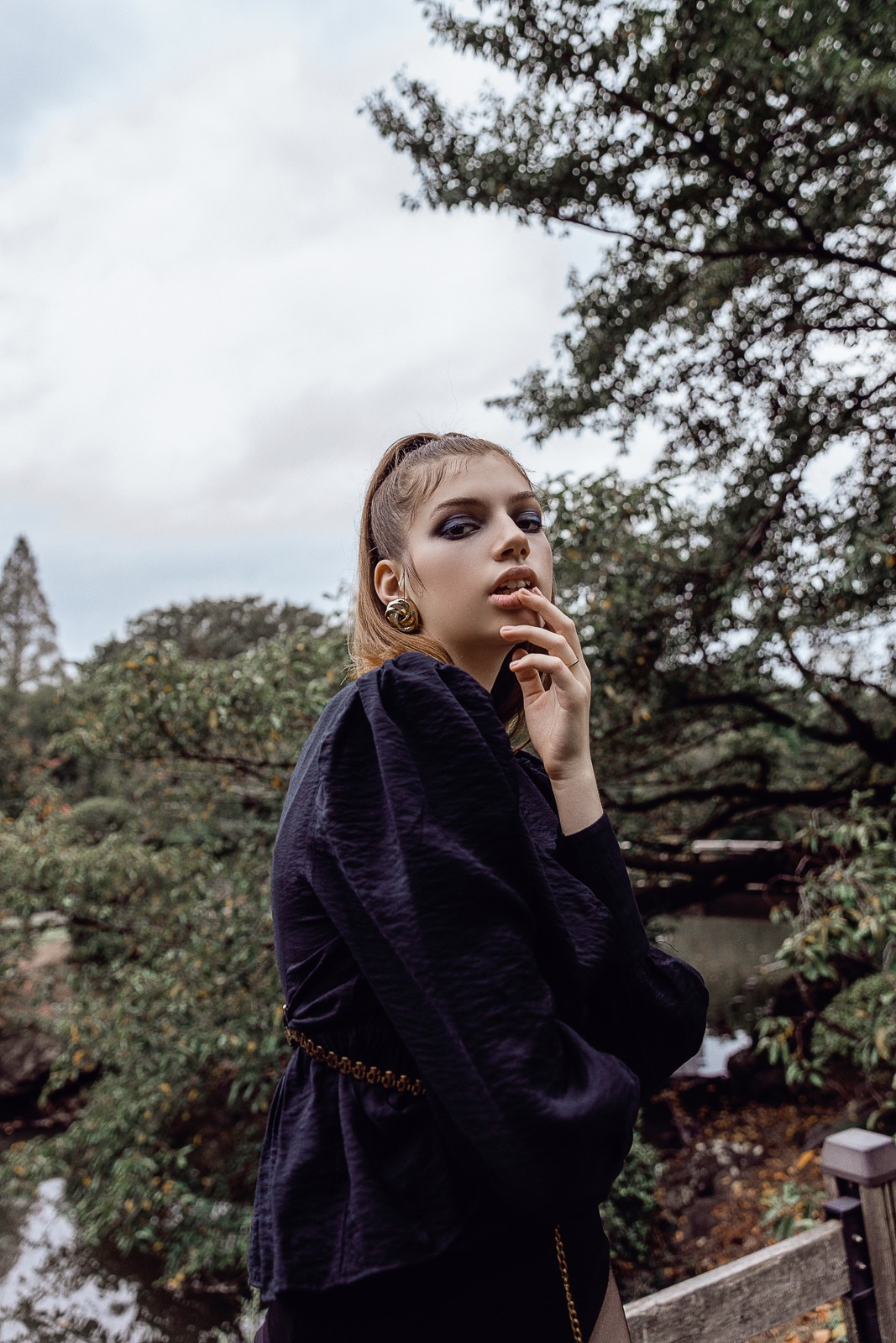 editorial portrait of fashion model wearing black jumpsuit and tights in shinjuku gyoen tokyo