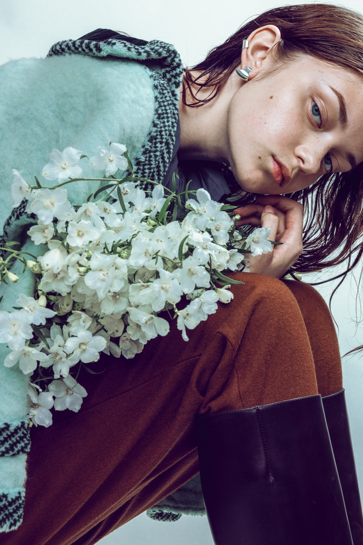 anmoda models tokyo alyona wearing a vintage pea coat and dlaw jewelry, holding flowers in a studio in tokyo